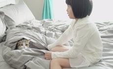 实拍床上小女孩与猫玩耍