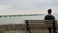 \[4K\]男孩坐在长凳上观看一望无际大海沉思海鸥海面飞翔高清视频